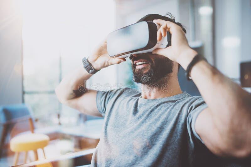 佩带虚拟现实风镜的有胡子的年轻人在现代coworking的演播室 智能手机使用与VR耳机在办公室 免版税库存照片