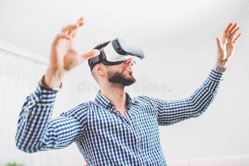 佩带虚拟现实风镜的英俊,有胡子的人在现代室内设计coworking的演播室 智能手机设置与VR风镜a 库存图片