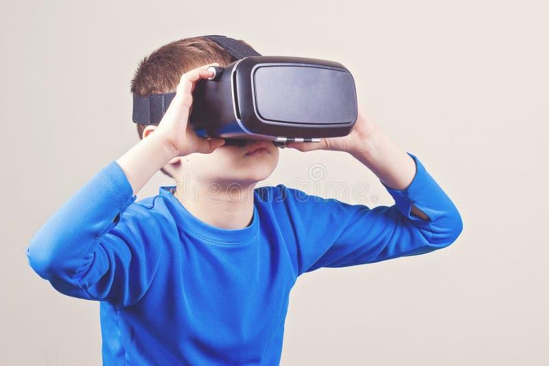 佩带虚拟现实风镜的青少年的男孩观看电影或打电子游戏 免版税库存照片