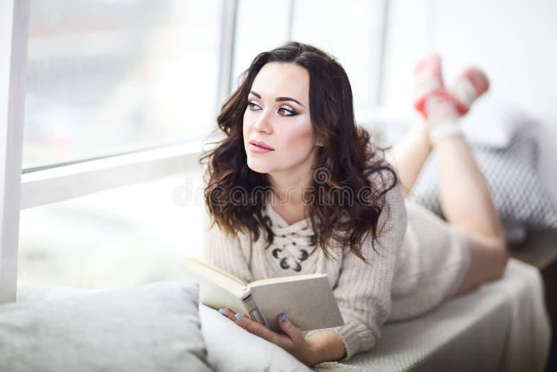 佩带被编织的毛线衣看书的年轻美丽的深色的妇女放松由窗口 免版税库存照片