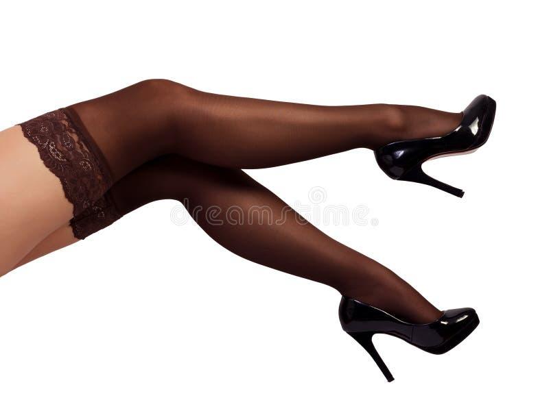 佩带裤袜和黑高跟鞋的性感的妇女腿 免版税库存图片
