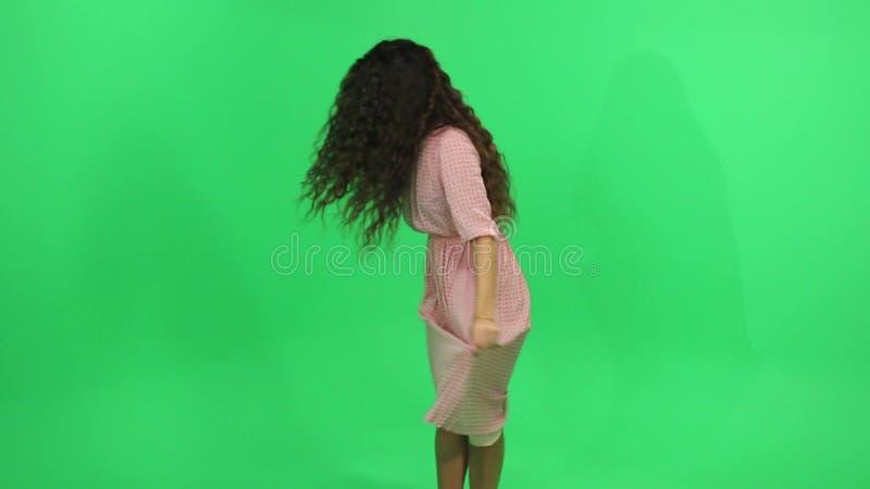 佩带象飞机的女孩桃红色礼服飞行在绿色屏幕上 股票录像