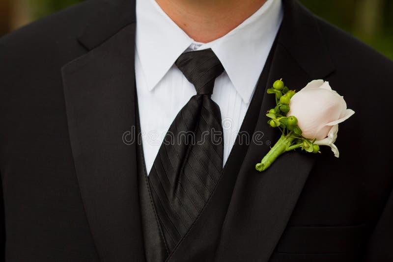 佩带钮扣眼上插的花的新郎在婚礼 免版税库存照片