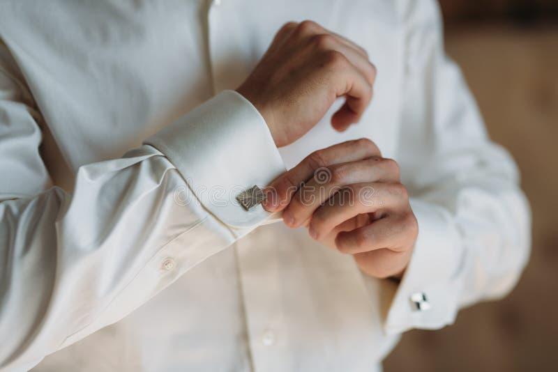 佩带链扣的新郎手 典雅的绅士clother、白色衬衣和棕色传送带 库存照片