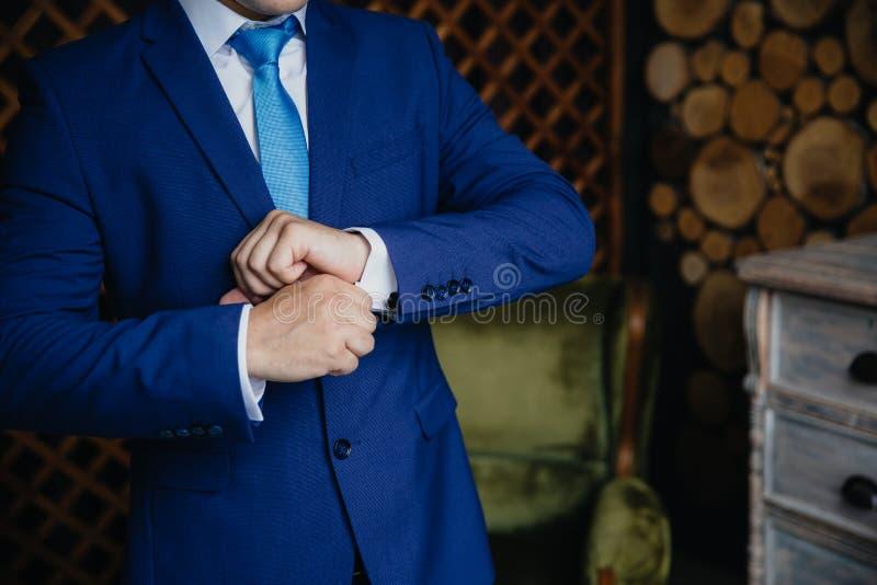 佩带链扣的新郎手 典雅的绅士clother,白色衬衣水兵 图库摄影