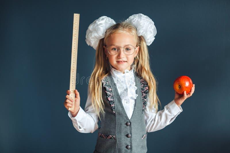佩带镜片的滑稽的女孩仿效一位严密的老师反对蓝色背景 r E ?? 库存照片