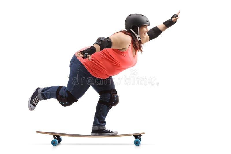 佩带防护齿轮的超重妇女乘坐longboard 库存照片