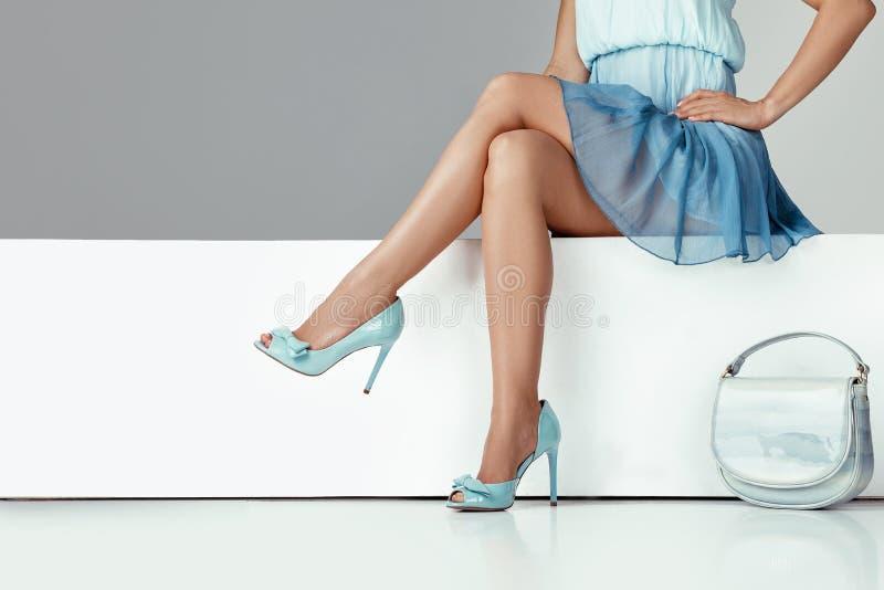 佩带高跟鞋的腿妇女穿上鞋子坐长凳 库存照片