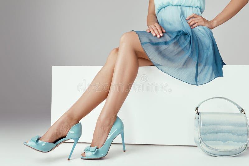 佩带高跟鞋的腿妇女穿上鞋子坐长凳 库存图片