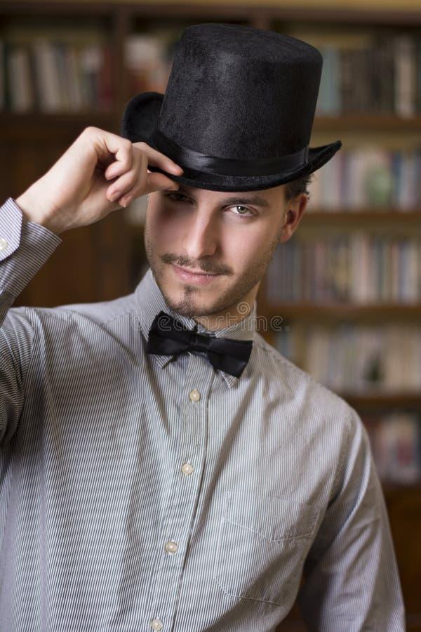 佩带高顶丝质礼帽和蝶形领结的可爱的年轻人 免版税库存照片