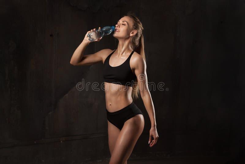 佩带黑体育穿戴standingon黑暗背景的肌肉年轻女运动员的图象 休息在workou以后的女子爱好健美者 库存图片