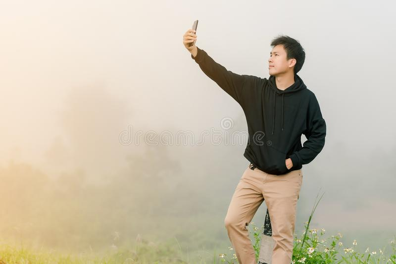 佩带黑冬天衣物立场的亚裔男孩少年为照相与在路的一个手机沿 库存图片