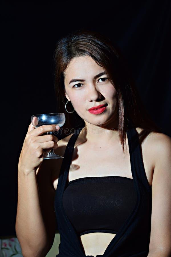 佩带黑无袖的举行的酒杯的美丽的亚裔西班牙中年妇女 库存照片