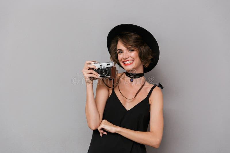 佩带黑礼服和帽子photogr的白种人妇女20s照片  库存照片