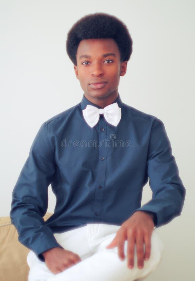 佩带黑衬衣和白色蝶形领结演播室画象的年轻人 库存图片