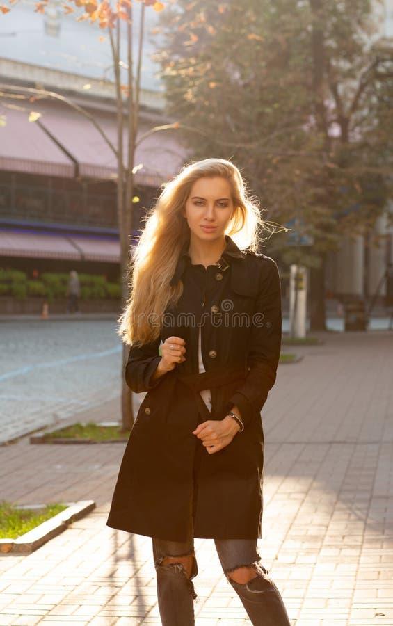 佩带黑co的美妙的白肤金发的模型晴朗的秋天画象  库存图片