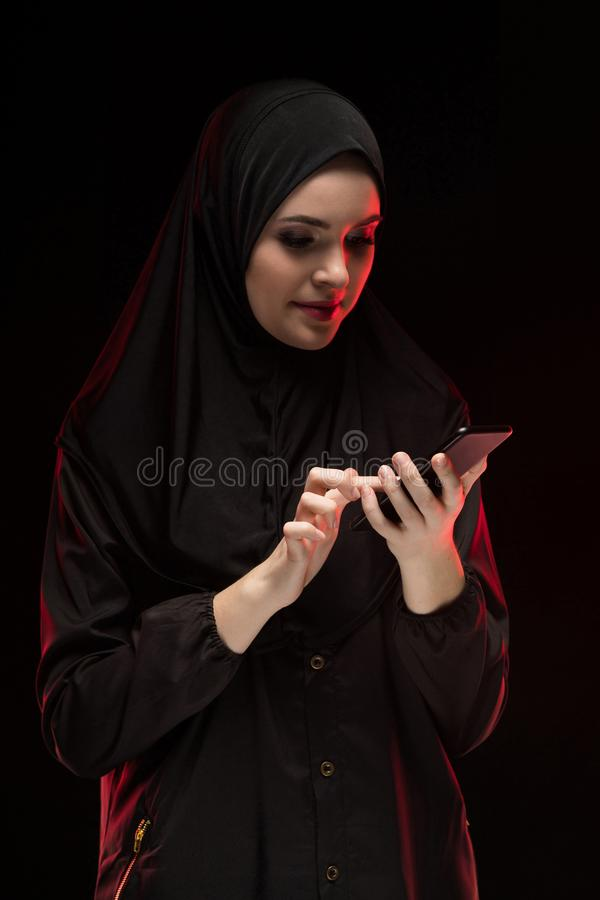 佩带黑hijab的美丽的正面友好的年轻回教妇女画象拿着在黑背景的手机 免版税库存图片
