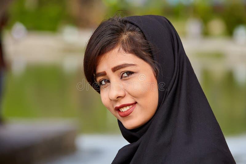 佩带黑hijab,伊斯法罕, I的微笑的伊朗女孩画象  库存照片