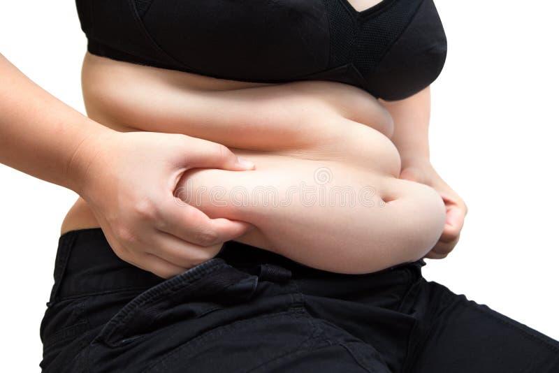 佩带黑内衣胸罩和气喘超重概念的肥胖妇女挤压腹部油脂 免版税库存图片