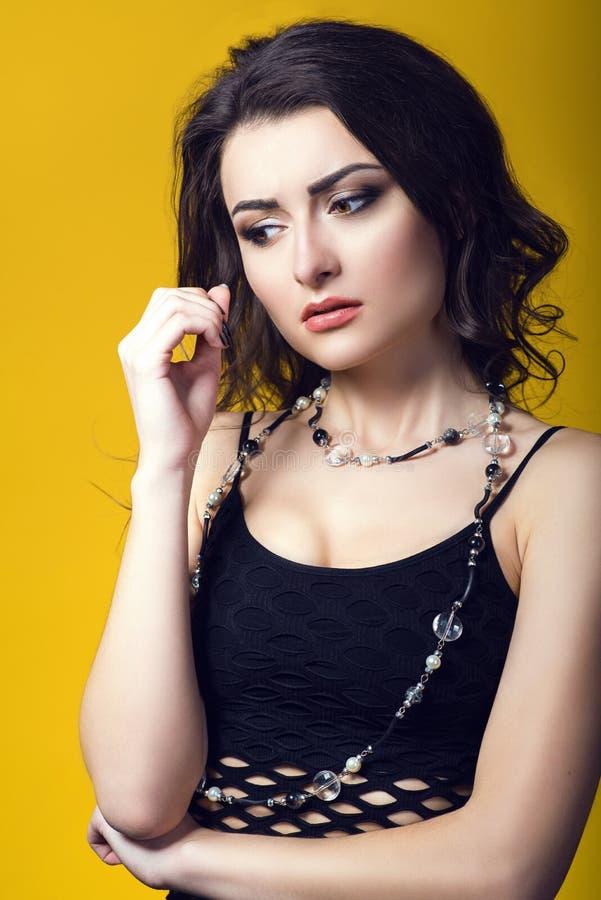 佩带黑净上面和玻璃珠的一名年轻美丽的深色头发的有关妇女的画象看起来担心和弄翻 免版税库存照片