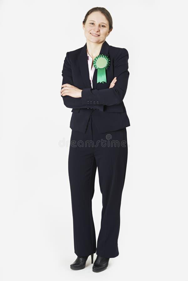 佩带绿色玫瑰华饰的女性政客全长画象 库存图片