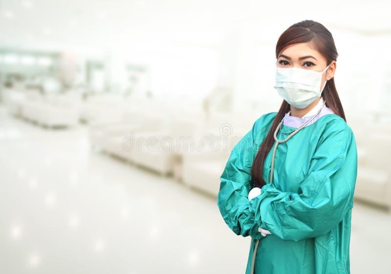 佩带绿色的女性医生在医院洗刷和听诊器 图库摄影