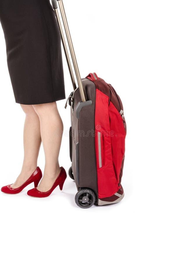 佩带黑铅笔裙子和泵浦的妇女拉扯一件小旅行行李#1 库存图片