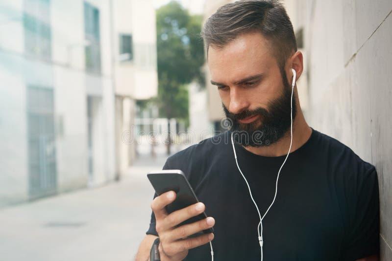 佩带黑T恤杉空白突然反弹盖帽夏时的有胡子的肌肉人 使用智能手机耳机看的年轻人 免版税库存照片