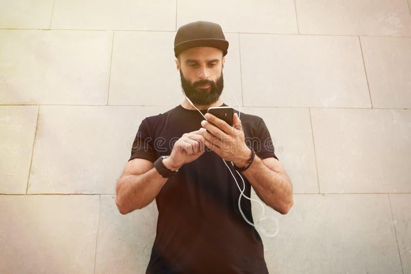 佩带黑T恤杉空白突然反弹盖帽夏时的有胡子的肌肉人 站立在空的灰色混凝土对面的年轻人 库存照片