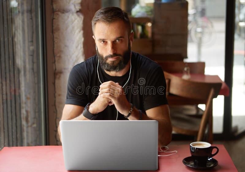 佩带黑T恤杉运作的膝上型计算机都市咖啡馆的英俊的年轻有胡子的商人 人坐的木表杯咖啡 库存图片