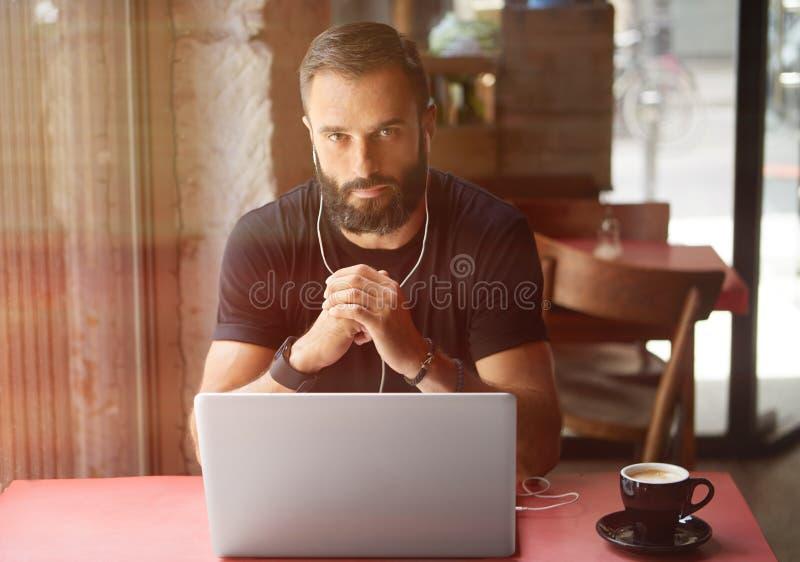 佩带黑T恤杉运作的膝上型计算机都市咖啡馆的年轻有胡子的商人 人坐的木表杯咖啡听 免版税图库摄影