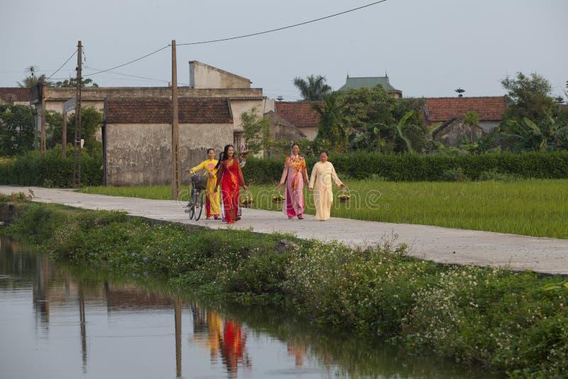 佩带Ao戴的基督徒越南妇女,当走到乡下公路的时教会 库存图片