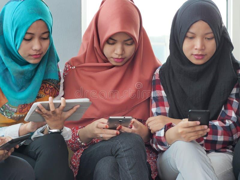 佩带hijab的三个女孩使用移动设备 免版税图库摄影