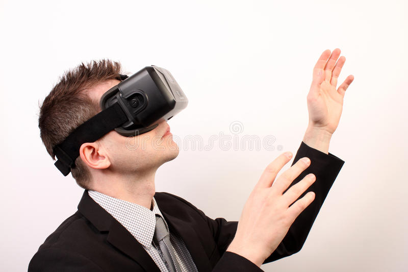 佩带VR虚拟现实Oculus裂口3D耳机的一个人的侧视图,接触某事用他的手,探索 免版税库存照片