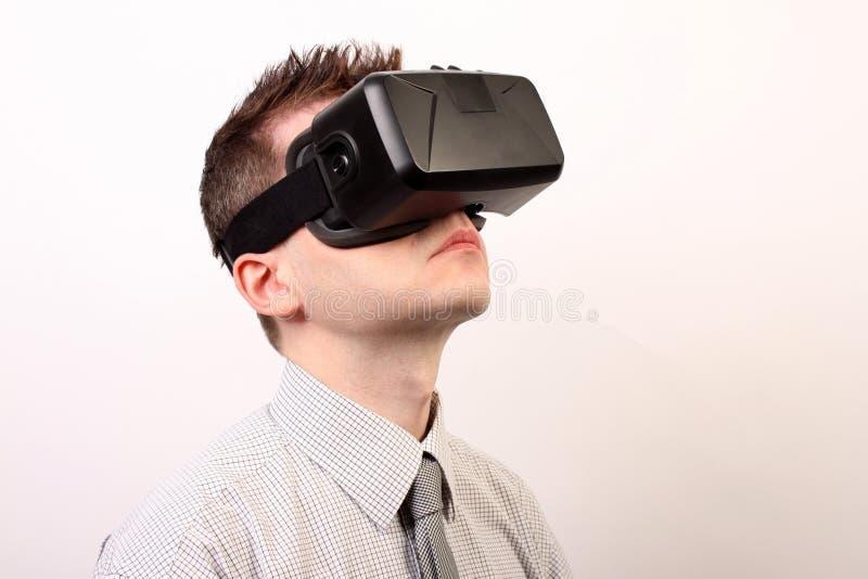 佩带VR虚拟现实Oculus裂口3D耳机的一个人的侧视图,看向上在一条正式衬衣和领带 免版税库存照片