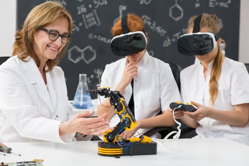 佩带VR风镜的教授和两名科学学生 图库摄影