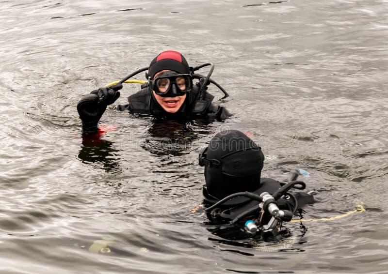 佩戴水肺的潜水在山湖,紧急救助者的实践的技术 浸没在凉水中 库存照片