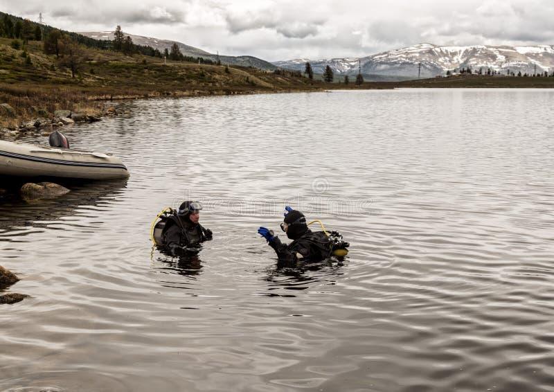 佩戴水肺的潜水在山湖,紧急救助者的实践的技术 浸没在凉水中 图库摄影