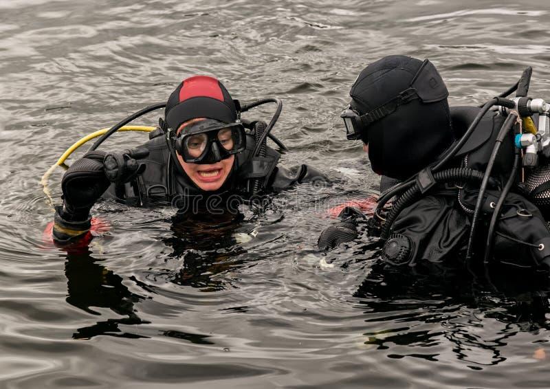 佩戴水肺的潜水在山湖,紧急救助者的实践的技术 浸没在凉水中 免版税图库摄影