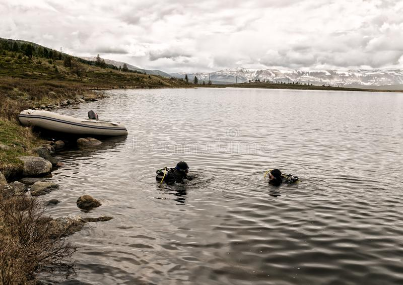 佩戴水肺的潜水在山湖,紧急救助者的实践的技术 浸没在凉水中 免版税库存图片