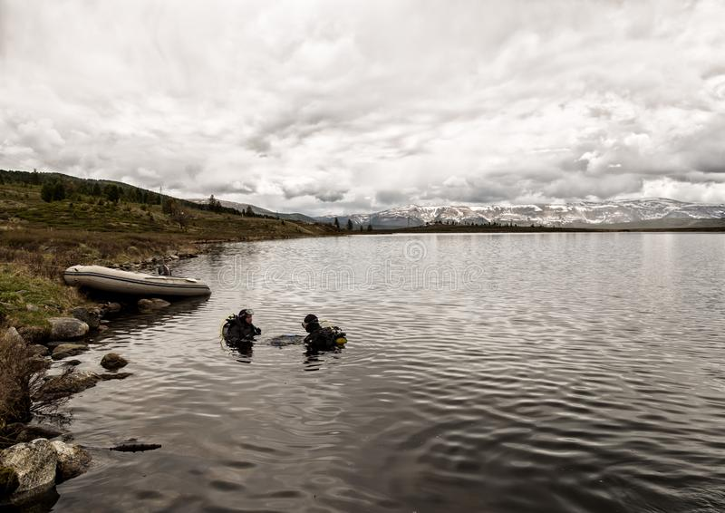 佩戴水肺的潜水在山湖,紧急救助者的实践的技术 浸没在凉水中 库存图片