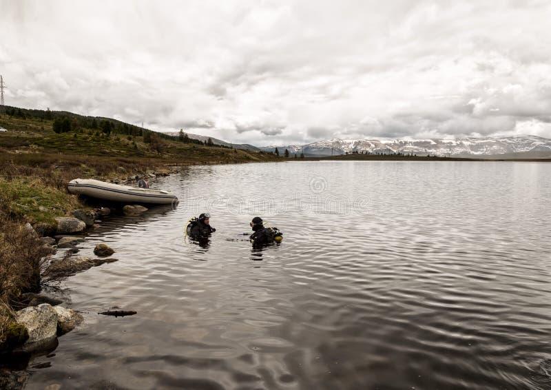 佩戴水肺的潜水在山湖,紧急救助者的实践的技术 浸没在凉水中 免版税库存照片