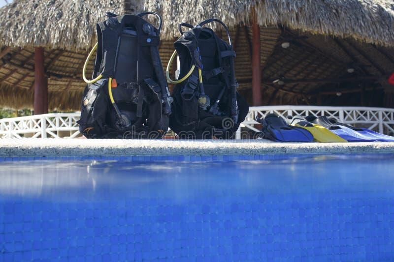佩戴水肺的潜水教训 在水池边缘的水肺 图库摄影