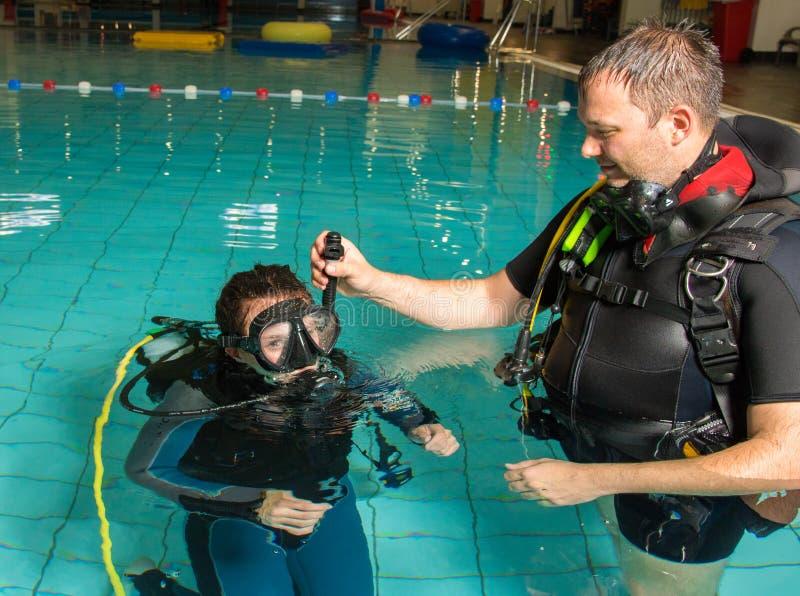 佩戴水肺的潜水路线水池有辅导员的少年女孩在水中 免版税库存照片