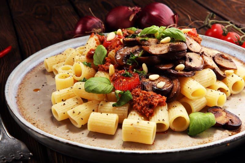 佩纳在西红柿酱的面团rigatoni用蘑菇、蕃茄装饰用荷兰芹和蓬蒿 免版税库存照片