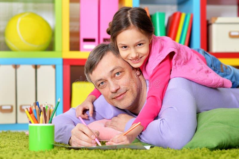 使一致愉快的父亲和他逗人喜爱的女儿画象  免版税图库摄影