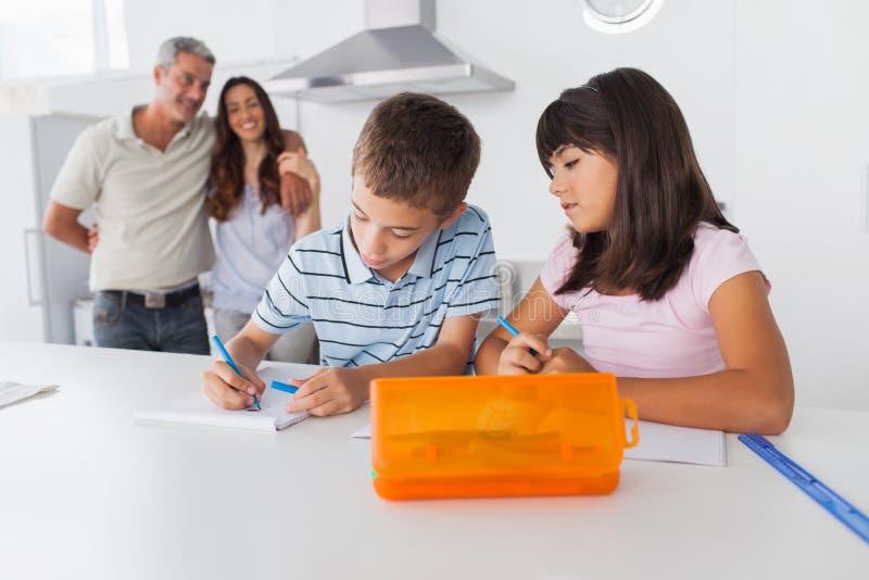 使一致在有他们父母微笑的厨房里的兄弟姐妹 免版税库存图片