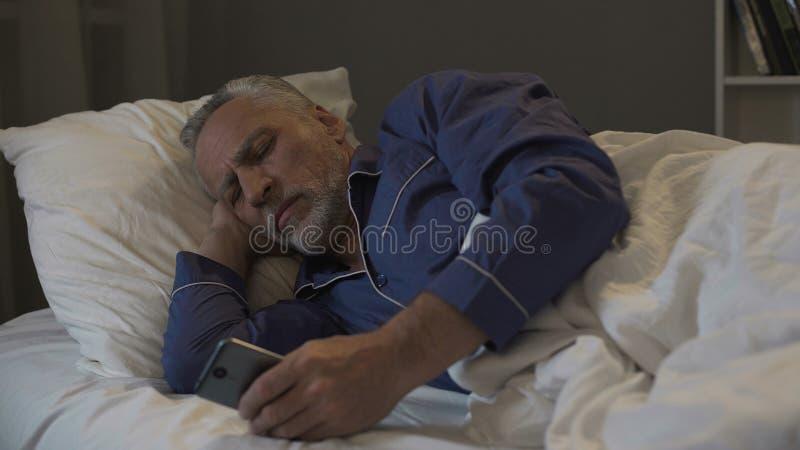 使上瘾对智能手机退休了人卷动应用而不是睡觉 免版税库存图片
