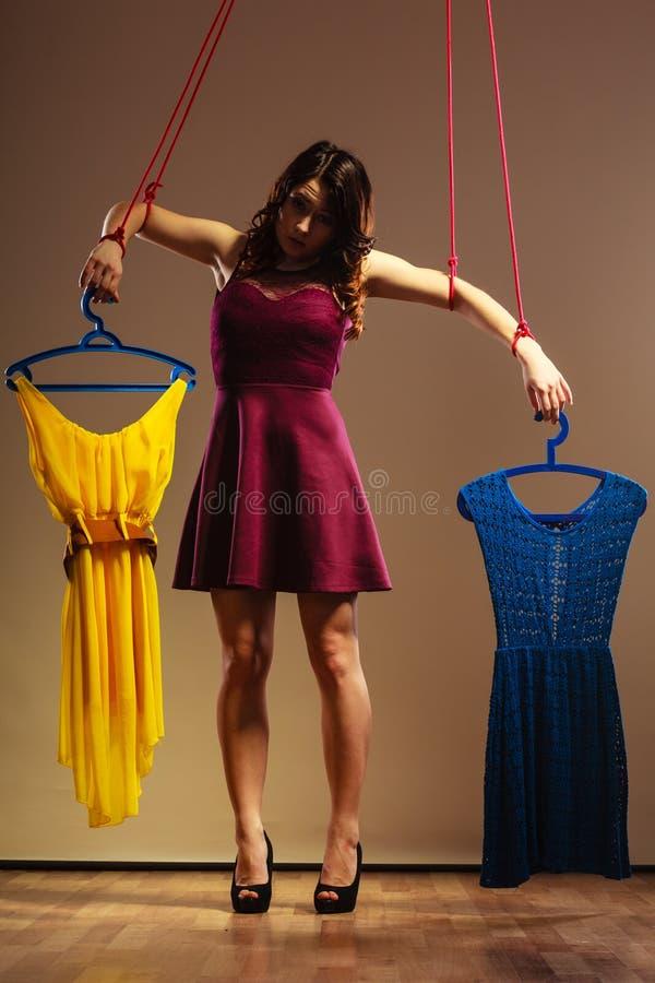 使上瘾对有衣裳的购物的妇女女孩牵线木偶 库存照片