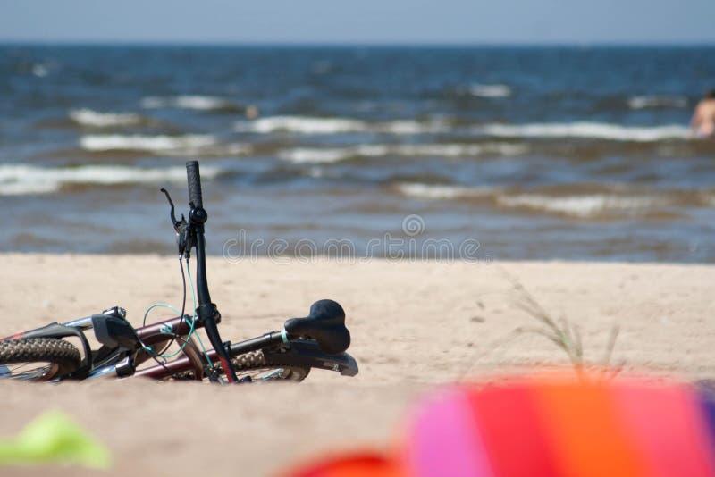 使与自行车、游泳的人民和毛巾的海视图靠岸 库存照片
